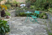 Green metal table and chairs on crazy paving patio, stone raised beds, Asplenium scolopendrium