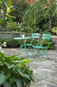 Green metal table and chairs on crazy paving patio, arum in container, stone raised beds, Cyrtomium fortunei