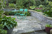 Green metal table and chairs on crazy paving patio, arum in container, stone raised bed, Cyrtomium fortunei
