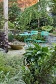 Green metal table and chairs on crazy paving patio, arum in container, stone raised beds