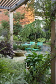 Green metal table and chairs on crazy paving patio, arum in container, stone raised beds, wooden pergola