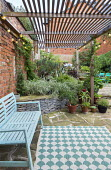 Slatted pergola over wooden bench and outdoor rug on crazy paving patio, stone raised bed, Phalaris arundinacea var. picta