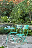 Green metal table and chairs on crazy paving patio, stone raised bed, Asplenium scolopendrium, Cyrtomium fortunei