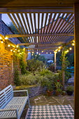 Bench on patio at night, string of lights on wooden pergola, outdoor rug