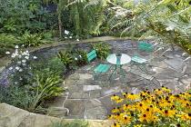 Stone raised beds around table and chairs on crazy paving patio, Rudbeckia fulgida var. sullivantii 'Goldsturm', Asplenium scolopendrium, Anemone x hybrida 'Honorine Jobert', Astelia nervosa 'Westland...