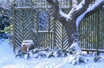 Garden shadows in snow with trellis and pot