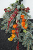 Spruce and Chinese lanterns tied with tartan ribbon bow