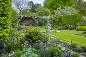 Stainless steel water feature by Arc Angel, Tulipa 'Blue Diamond', hornbeam hedges, bench under pergola against brick wall
