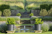 Formal pool and fountain in sunken garden, Lavandula angustifolia 'Princess Blue', Viburnum tinus in large containers, stone walls and steps