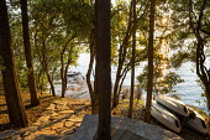 View through oak trees, Quercus ilex, to seashore, stone path, jetty, boats