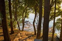 View through oak trees, Quercus ilex, to seashore, stone path, jetty