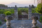Metal gate between stone piers, stone walls, view to Mount Etna
