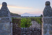 Metal gate between stone piers, view to Mount Etna