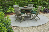 Wooden table and chairs on circular patio in London front garden, Cor-Ten steel border edging
