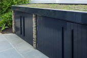 Black painted storage sheds with living green roof