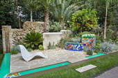 Contemporary chair on crazy paving patio, stone wall, rill and fountain, colourful mosaic built-in bench, Citrus sinensis, Opuntia ficus-indica, Cycas revoluta