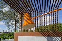 Metal pergola screen over contemporary roof terrace, Quercus suber, large orange lamp