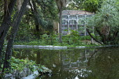 View across reflective pool to orangery in shady mediterranean garden