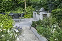 Table and chairs on patio by outdoor kitchen, cooking range and worktop, Aquilegia vulgaris 'Nivea', Hydrangea aspera Villosa Group, Geranium 'Brookside', Hydrangea arborescens 'Annabelle', Aquilegia...