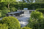 Table and chairs on patio by outdoor kitchen, cooking range and worktop, clipped mound of Prunus lusitanica, Hydrangea arborescens 'Annabelle', Hydrangea aspera Villosa Group