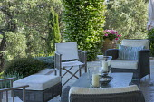 Chairs with cushions on terrace, candles, Trachelospermum jasminoides