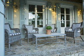 Wicker chairs with cushions around table on verandah