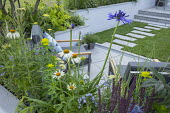 Chairs with blue cushions on enclosed sawn sandstone patio, Salvia 'Caradonna', Agapanthus 'Navy Blue', Achillea 'Credo', Euphorbia wallichii, Amsonia orientalis and Echinacea 'White Swan' in raised b...
