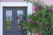 Traditional Corfiot front doors with glass panes with decorative wrought-iron grilles