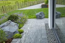 Stone paving around house, large rocks, geraniums