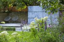 Agastache 'Blackadder', Selinum wallichianum, Verbena bonariensis, zinc coated galvanised steel wall panel, contemporary chairs on decking