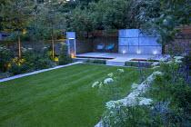 Zinc coated galvanised steel wall panel, stone bridge across formal rectangular pool, contemporary chairs on decking, formal lawn, water wall fountain, Selinum wallichianum, Agastache 'Blackadder'