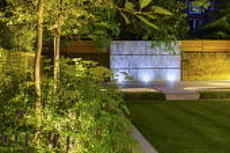 Rectangular lawn, row of uplit Amelanchier 'Robin Hill', zinc coated galvanised steel wall panel, Selinum wallichianum