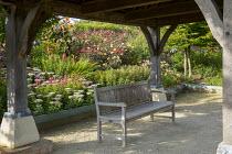 Wooden bench under timber gazebo, perennial border, Hylotelephium spectabile Brilliant Group 'Brilliant' syn. sedum, Dahlia 'Bishop of Llandaff', Ricinus 'New Zealand Black'