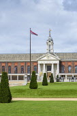Row of yew topiary in formal lawns in front of Royal Hospital, cannons, flag pole