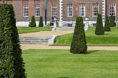 Wide gravel paths, stone steps, row of yew topiary in formal lawns in front of Royal Hospital