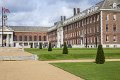 Wide gravel paths, stone steps, row of yew topiary in formal lawns in front of Royal Hospital, flag pole