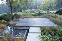 Square deck overhanging formal raised pebble pools, Carex testacea