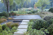 Stone path leading across border to square deck overhanging formal raised pebble pools, Carex testacea, Hakonechloa macra, clipped yew domes