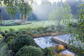 Square deck overhanging formal raised pebble pool, clipped yew mounds, Carex testacea