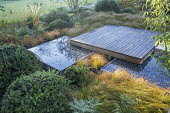 Square deck overhanging formal raised pebble pools, clipped yew mounds, Carex testacea groundcover