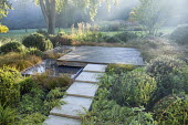 Stone path leading across border to square deck overhanging formal raised pebble pools, clipped yew mounds, Hakonechloa macra, Carex testacea, Calamagrostis x acutiflora 'Karl Foerster'