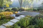 Stone path leading across border to square deck overhanging formal raised pebble pools, clipped yew domes, Carex testacea, Calamagrostis x acutiflora 'Karl Foerster', Hakonechloa macra
