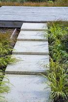 Stone path leading across border to square deck, Carex testacea, Hakonechloa macra