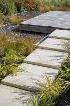 Stone path leading across border to square deck overhanging formal raised pebble pools, Carex testacea, Hakonechloa macra
