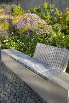 Built-in wooden bench, Rosa 'Apfelblüte', Sesleria autumnalis, Aster dumosus 'Zwergenhimmel', Aster trifoliatus subsp. ageratoides 'Asran', stone sett paving