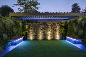 Contemporary adjustable pergola, lit stone wall water cascade, astroturf lawn, built-in benches with underlighting, living green walls, Carex oshimensis 'Evergold'