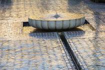 Ceramic mosaic zellij tile paving around circular bubbling fountain in mediterranean courtyard, marble basin
