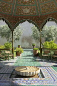 Ceramic mosaic zellij tile paving around circular bubbling fountain in mediterranean courtyard, marble basin, glazed green bejmat tile paving, chairs under ornate arbour, olive and lemon trees