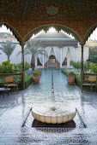 Ceramic mosaic zellij tile paving around circular bubbling fountain in mediterranean courtyard, marble basin, glazed green bejmat tile paving, chairs under ornate arbour