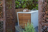 View through laser cut screen to outdoor kitchen, copper kettle and pans on cooker, cupboards, living green vertical edible wall, Lactuca sativa 'Lollo Rossa', 'Little Gem' and 'Merveille des Quatre S...